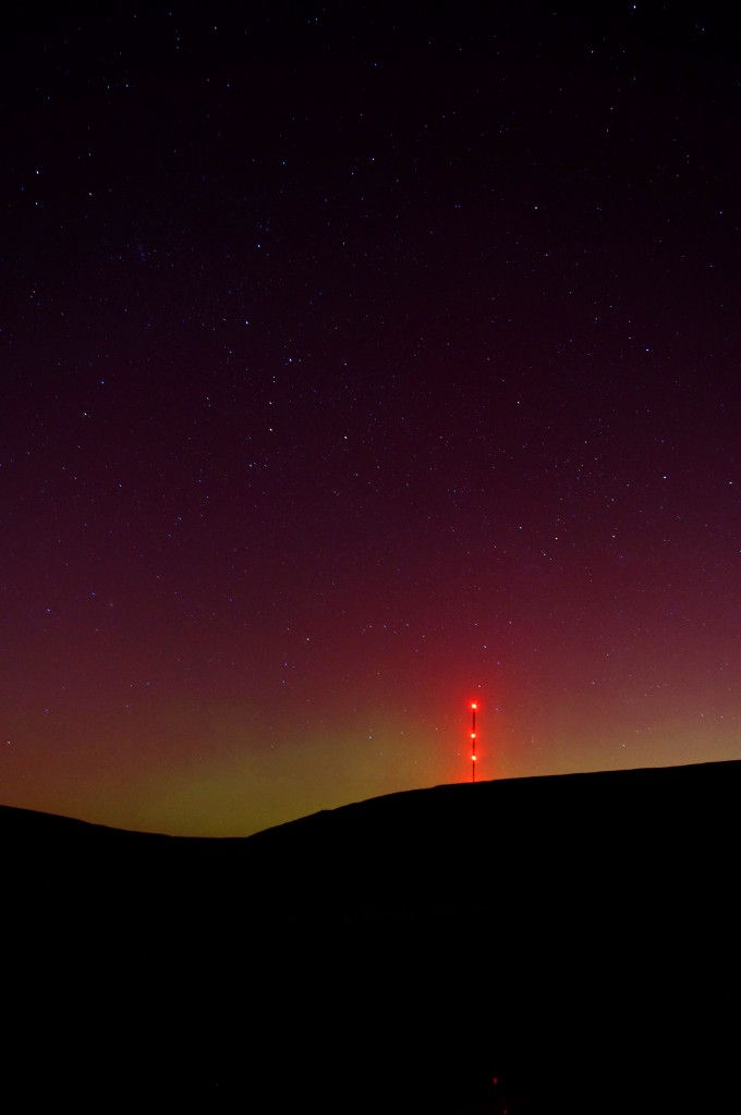 The green aurora with the red aurora above and, in the foreground, the Holme Moss transmitter station.
